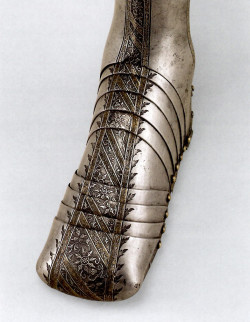 Fig. 2. Attributed to Wolfgang Grosschedel, detail of left greave with sabaton and spur (c. 1550), acid-etched steel with blackening and gilding, 48 x 35 cm, weight 2 1/2 bs. George F. Harding Collection, 1982.2695.