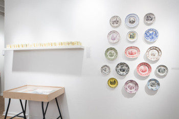 """""""Ephemeral Sprawl"""": installation view. Left: Emmett Ramstad, 1995 (2013), cash register receipt rolls from Giovanni's Room bookstore, Philadelphia; Right: England and France, earthenware (1800-50), underglaze transfer printed from engraving, fired, clear glazed and fired again, Collection of Andrew Raftery and Ned Lochaya. In case, clockwise from upper right: Girl Scout Handbook and Badges from the collection of Sinéad Cahill; Sinéad Cahill, Merit Badges (2013), lithographs on cotton, with embroidery; Sinéad Cahill, Handbook, (2013), cyanotype; Bakery business cards from the collection Erika Piola; Italian language guides from the collection of Rachel D'Agostino. Courtesy The Print Center, Philadelphia and Printeresting. Photo credit: James B. Abbott."""
