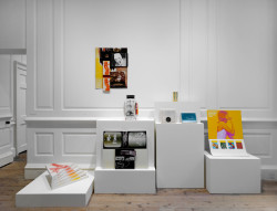 """Installation view: """"KP Brehmer. Real Capital Production,"""" Raven Row, 2014. From left to right: Start 3 (1968) laminated print on card, six parts, 55 × 40 × 3 cm each; Hommage à Berlin (Homage to Berlin) (1965) print on card, metal, 40 × 20 × 23 cm. Block Collection; Aufsteller: Ohne Titel (Display: Untitled) (1965), laminated print on card, 64 × 50 × 5 cm; Ohne Titel (Untitled), (1965), laminated print on card, boxes, book, 68 × 56 × 2 cm; Schachtel 'Für Beuys'  (Box 'For Beuys') (1965) laminated printed paper, collage on card, 14 × 6 × 6 cm; Schachtel (Box) (1966) laminated print on card, film stock, 22 × 23 × 2 cm; Schachtel (Box) (1966), laminated print on card, 15 × 21 × 2 cm; Aufsteller 25. Das Gefühl zwischen Fingerkuppen… (Display 25. The Feeling Between Fingertips…) (1967), print on card, plasticised surface, seed packets, 70 × 50 × 36 cm. All works courtesy Estate of KP Brehmer, Berlin, unless otherwise stated. Photo: Marcus J. Leith."""