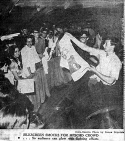 Newspaper photograph taken at 1969 premiere of HPSCHD showing screenprinting of smocks and other garments with the Beethoven/Cage design being distributed to the audience. Reproduced by permission of The News-Gazette, Inc. Permission does not imply endorsement.